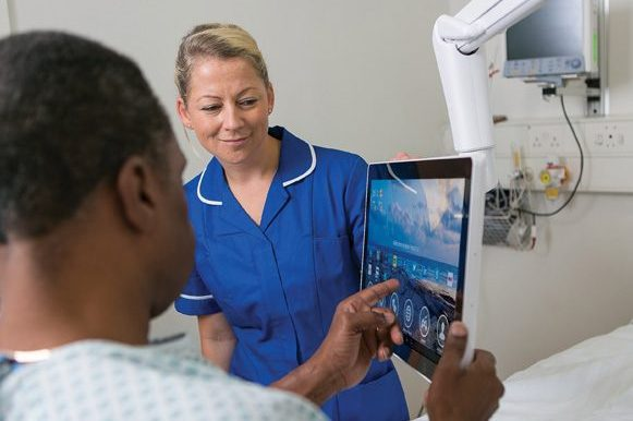 Female nurse looking at screen of bed side tablet