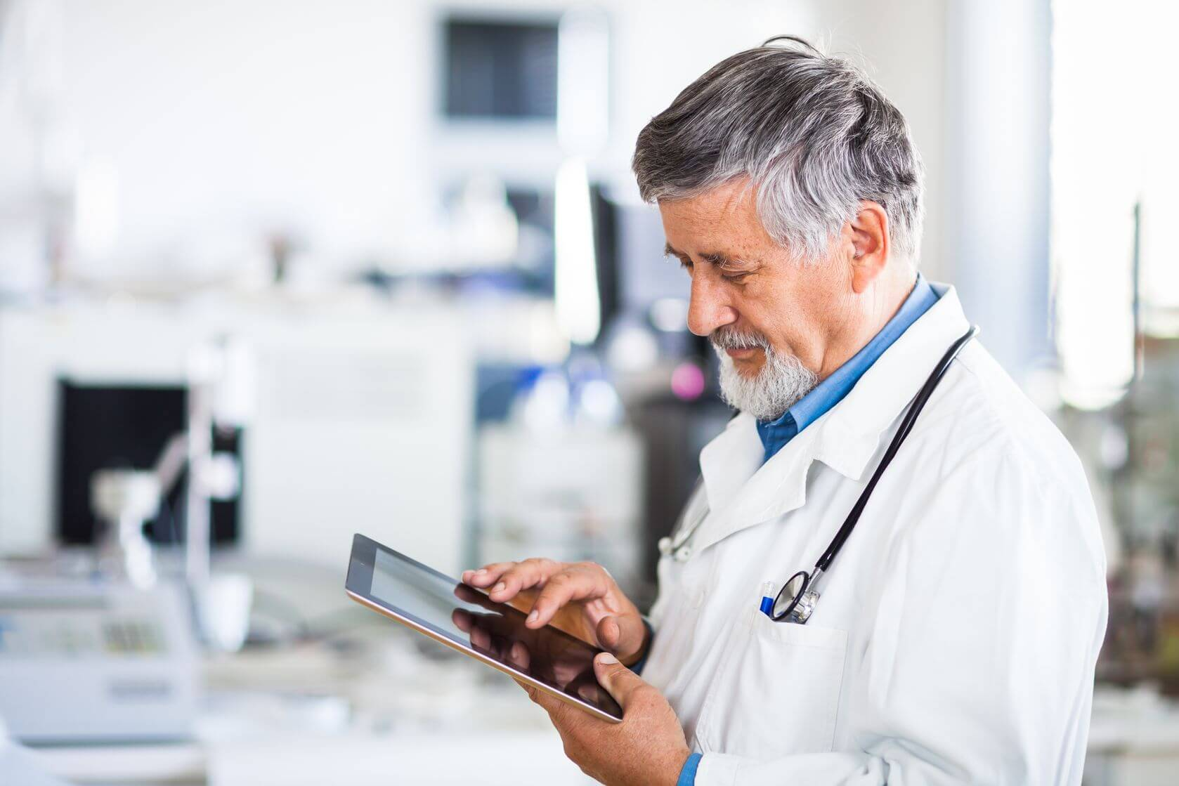 Male doctor looking at digital tablet screen