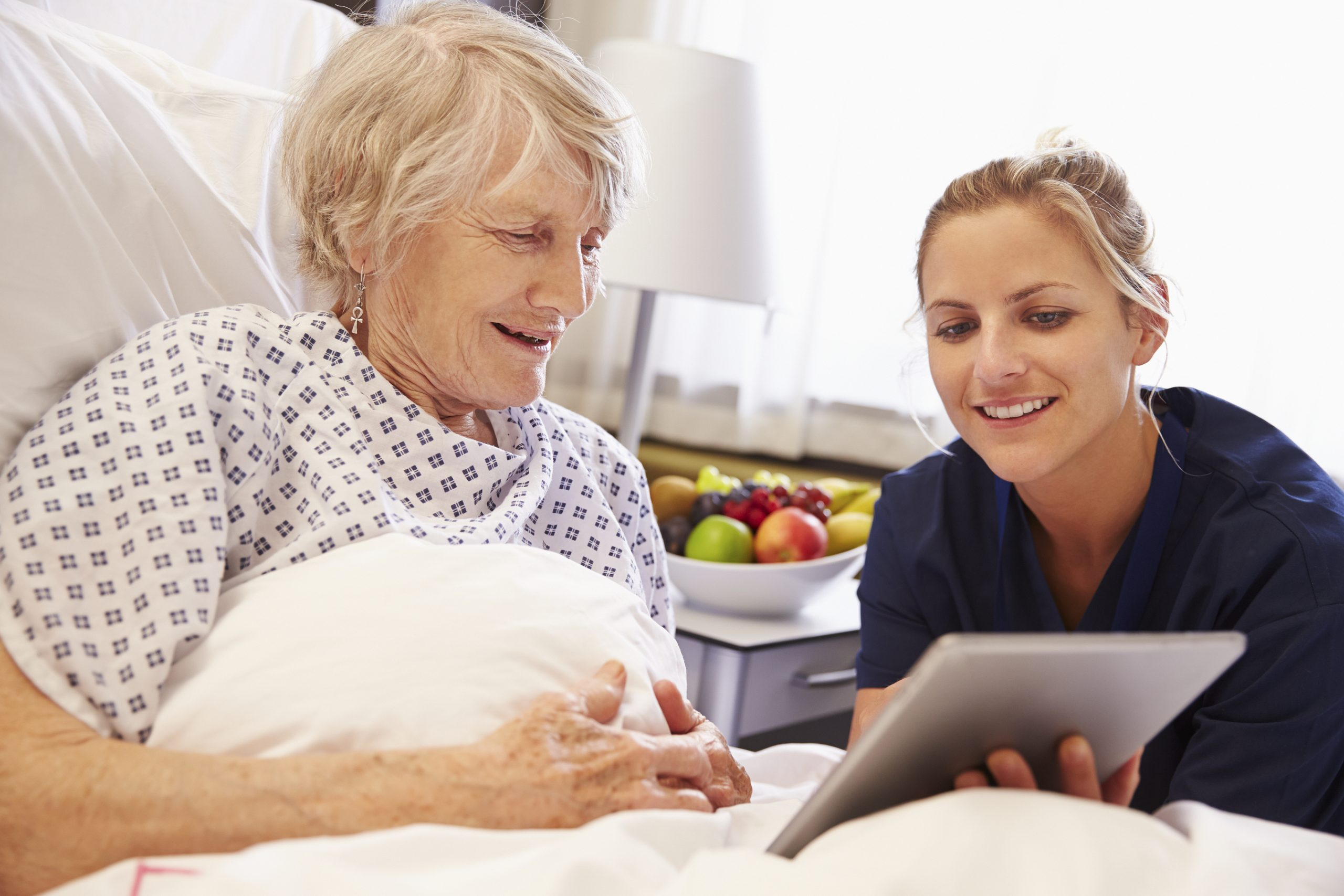 Elderly female patient looking at a tablet screen with nurse