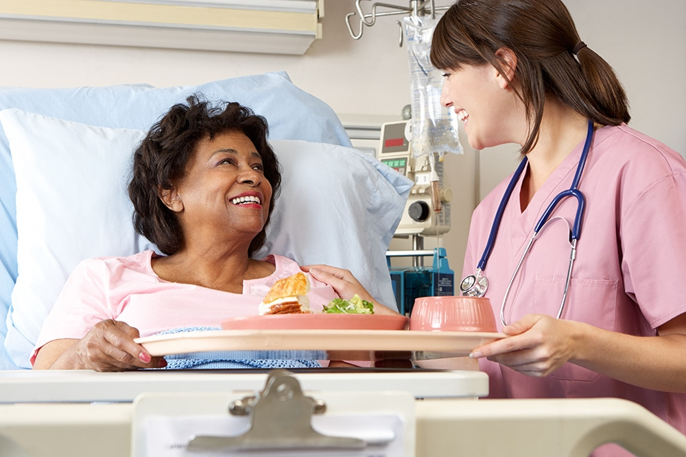 Female nurse delivering food to female patient in hospital bed
