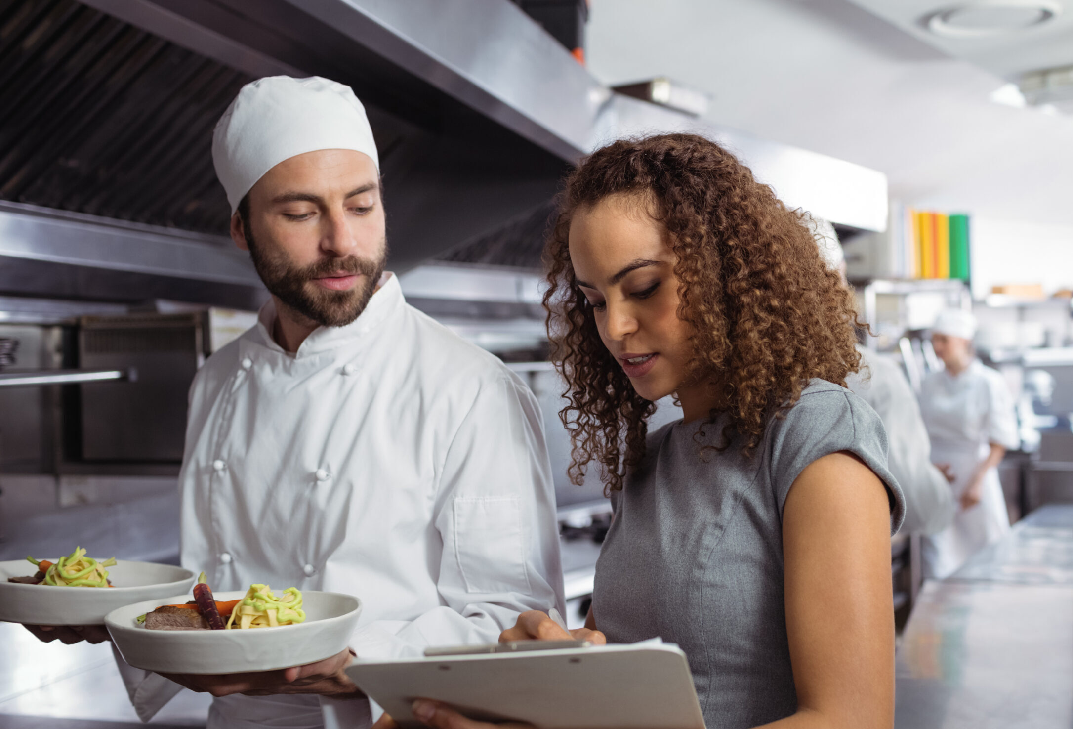 Consultant talking to chef with clipboard
