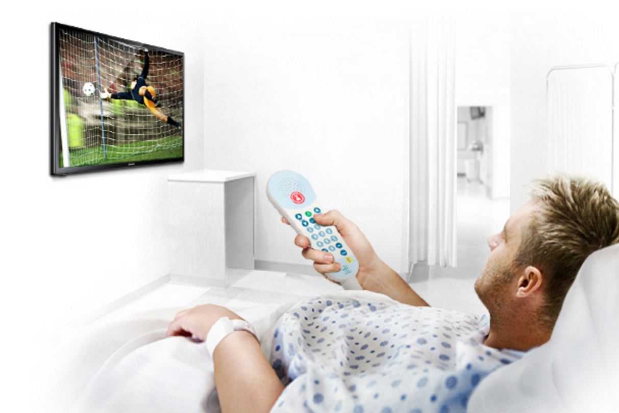 Male patient in bed changing channels