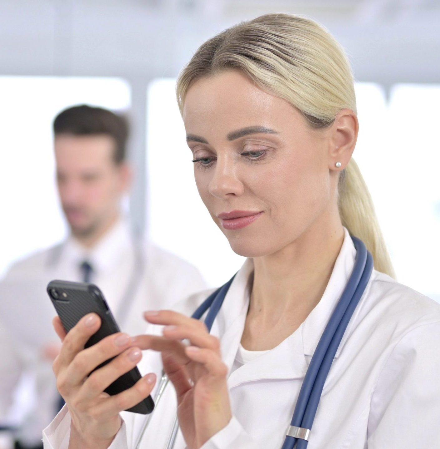 Focused female doctor using Smartphone