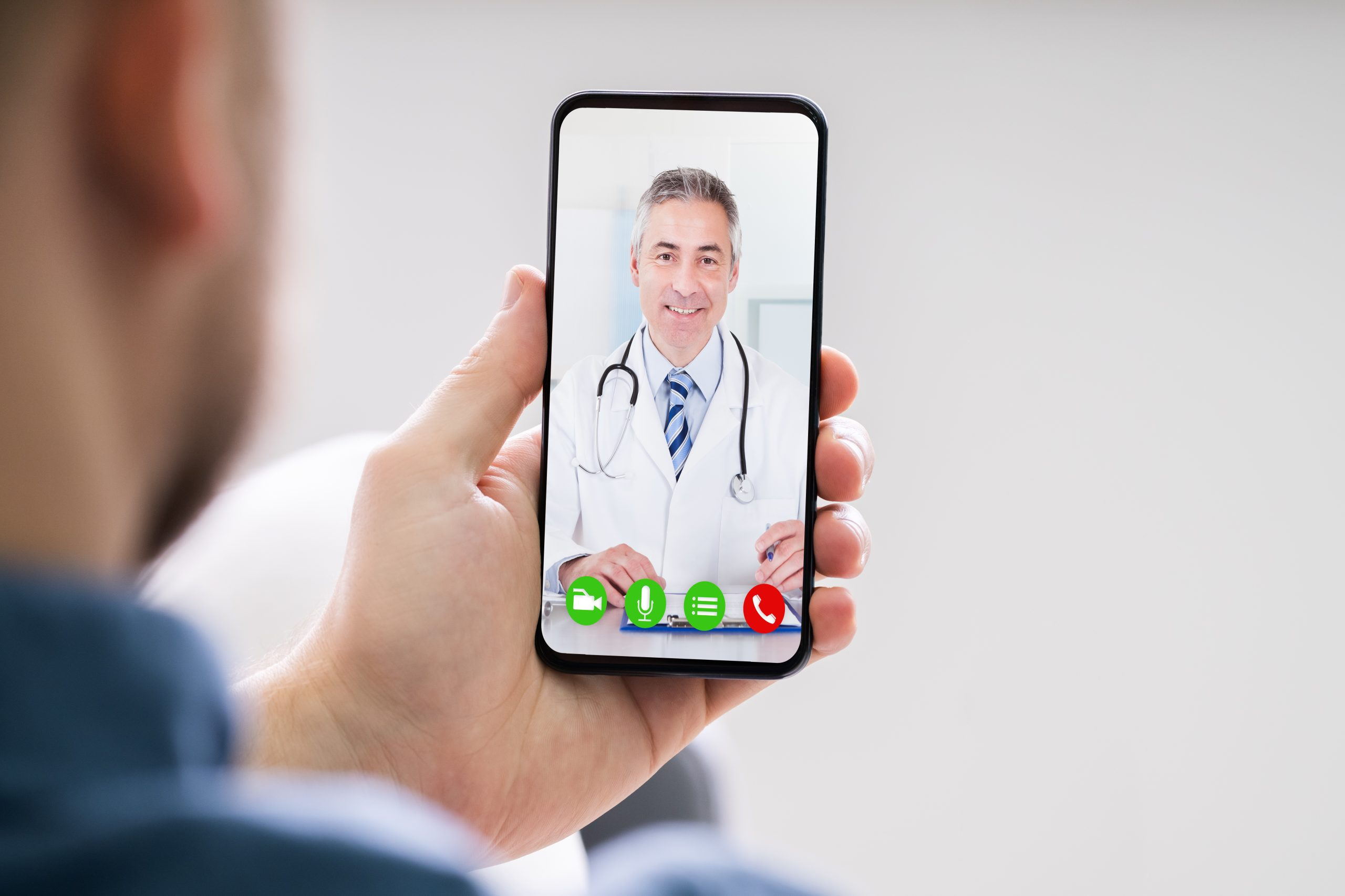 Male holding phone and talking to doctor virtually