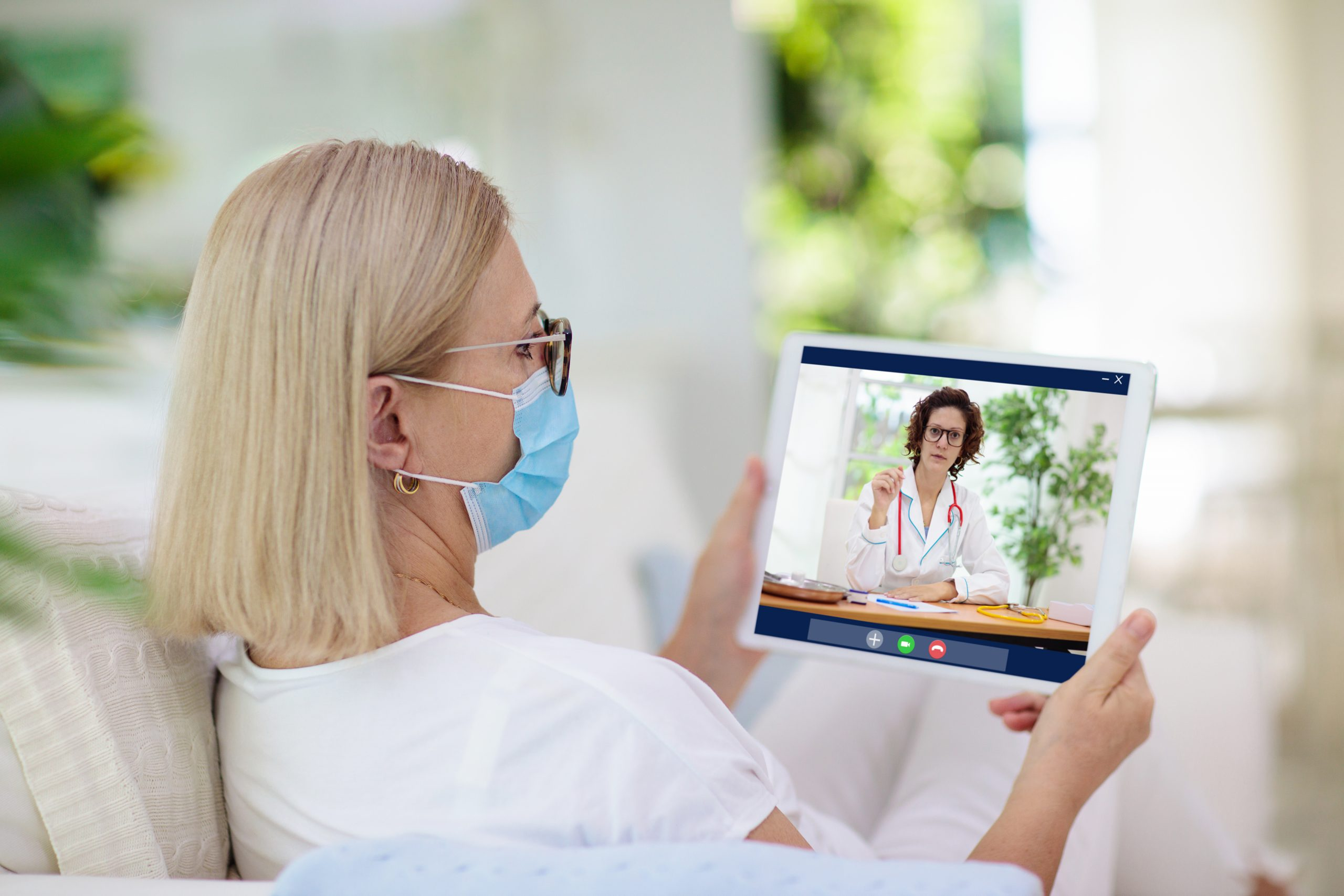 Masked female talking to a doctor virtually